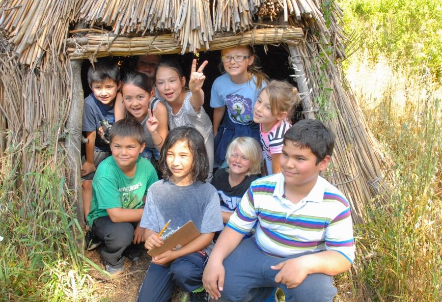 Students explore the tule reed hut.
